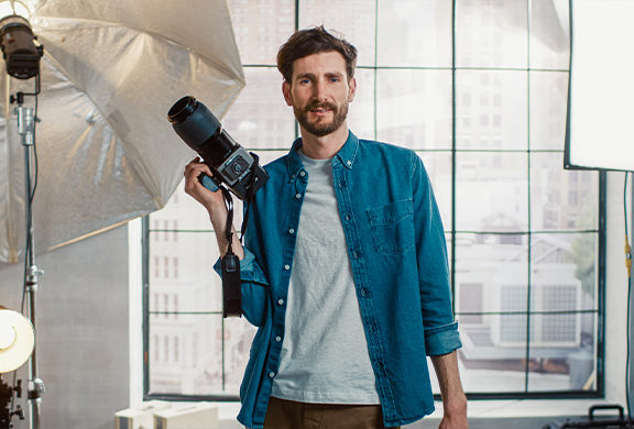 man holding camera with light lamp near him. He has dark hair and beard. He is wearing a blue unbuttoned down shirt with a white t-shirt underneath.