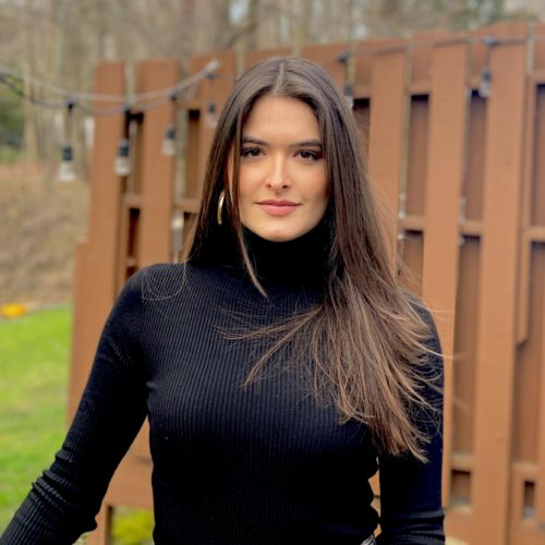 Elisa Masiero wearing a black turtleneck sweater, has long brown hair