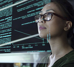 photo of a young woman looking at see through data whilst seated in a dark office
